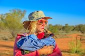 Tourist woman holding orphaned baby kangaroo in Australian outback, bush landscape. Interacting with cute kangaroo orphan. Australian Marsupial in Northern Territory, Central Australia, Red Centre. poster