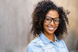 Happy smiling young woman with eyeglasses and denim shirt looking at camera. Black girl feeling successful standing against wall with copy space. African student smiling and wearing spectacles.