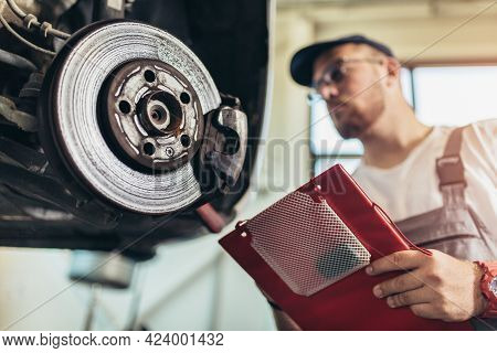 Professional Near The Car Hanging On The Lift At The Service Station Make A Diagnostics, Repair The
