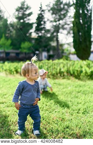 Small Child With A Ponytail Stands On A Green Lawn And Looks To The Side