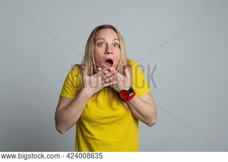 Portrait Of Scared Mature Woman With Hands Near Face, Wearing Casual Yellow T Shirt. Studio Shot, Gr