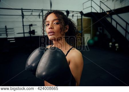 African American Female Boxer Training At The Gym With Boxing Gloves On. Mixed Race Female Holding B