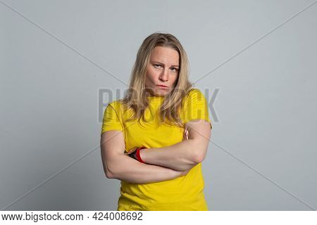 Displeased Mature Woman Wearing In Casual Yellow T Shirt Frowning And Looking At Camera. Studio Shot