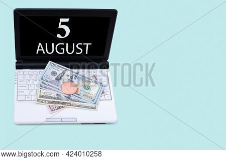 5th Day Of August. Laptop With The Date Of 5 August And Cryptocurrency Bitcoin, Dollars On A Blue Ba