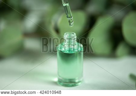 The Drop Of Eucalyptus Oil Hangs From Pipette, Pouring Herbal Essence Oil Into The Glass Dropper Bot