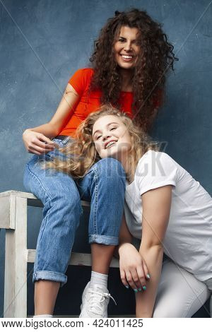 Young Pretty Teenage Girls Friends With Blond And Brunette Curly Hair Posing Cheerful On Blue Backgr