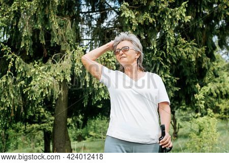 Senior Woman Hiking Outdoors. Smiling Mature Woman Standing With Nordic Walking Sticks In Forest, Su