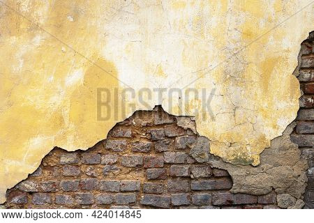 Background With An Old Wall With Crumbling Plaster Painted With An Orange Paint And Exposed Bricks