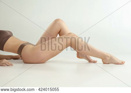 Beautiful Female Legs Isolated On White Background. Beauty, Cosmetics, Spa, Depilation, Treatment An