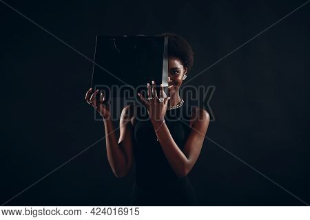 African American Woman With Afro Hairstyle Smiles And Holds Black Shopping Bags. Sale And Discounts