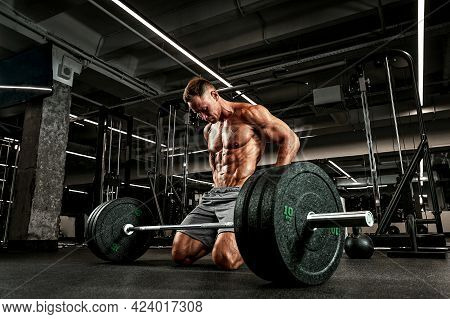 Atelt With A Beautifully Sculpted Body Is Preparing To Do Exercises With A Barbell. The Athlete Prep