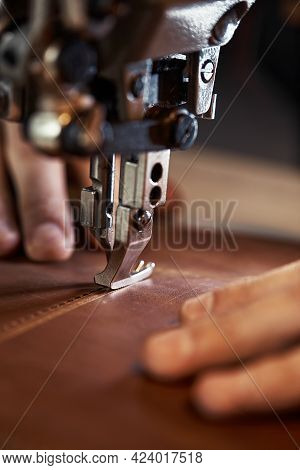 A Sewing Machine Foot With The Hands Of A Master Close-up, A Tailor Makes A Seam On A Piece Of Leath