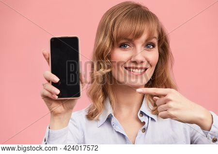 Girl With A Phone In Her Hands Points To The Screen With Her Finger, Pink Background, Close-up, Conc
