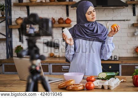 Arabian Female Food Blogger Comparing Supplements And Natural Food