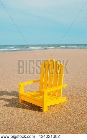 a yellow miniature chair on the sand of a lonely beach, with the sea in the background and some blank space on top