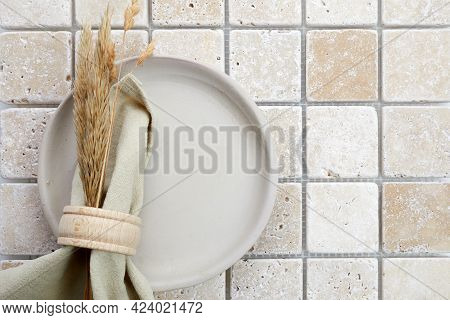 Stylish Serving On A Travertine Mosaic Background. Linen Napkin On Plate. Top View