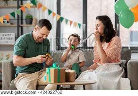 family, holidays and people concept - happy mother, father and little son with gifts and party blowers having fun and celebrating birthday at home