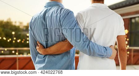 homosexuality, same-sex marriage and lgbt concept - close up of happy male gay couple hugging from back over roof top party background