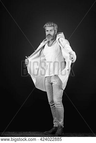 Handsome Man Wearing Jeans Pants And A Coat Posing At Studio. Mens Beauty, Seasonal Fashion. Studio