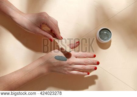 beauty, cosmetics and bodycare concept - hands with wooden spatula applying blue cosmetic clay mask to skin on beige background
