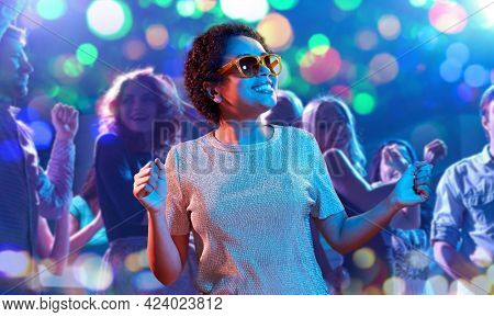 leisure, clubbing and nightlife concept - smiling young african american woman in sunglasses dancing in ultraviolet neon lights over nightclub background