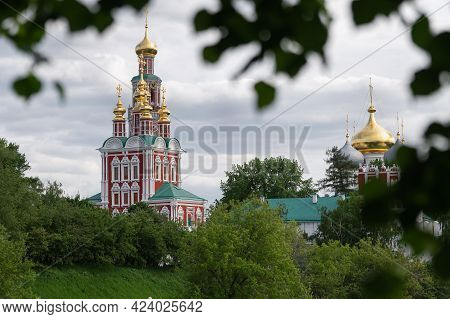 View Of The Moscow Novodevichy Monastery In Spring Evening With Blurred Tree Leaves On The Foregroun