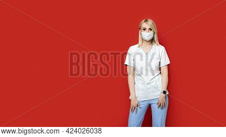 Confident Female Doctor Wearing Protective Face Mask Standing On Red Background. Young Woman Intern