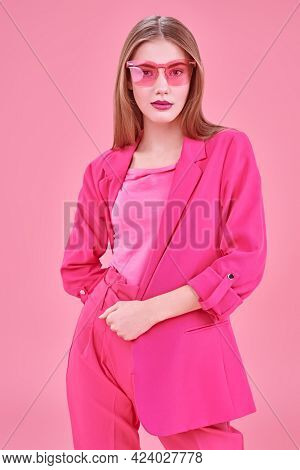 Beautiful fashion model posing at studio in trendy crimson suit and sunglasses on a pink background. Glamorous pink style.