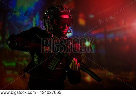 Virtual reality, city of the future. A tech cyber warrior fights with a gun in his hands against the backdrop of the night city.