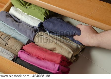 Concept Vertical Japanese Clothes Storage System. Multicolored Shirts Stacked In A Dresser Shelf Usi