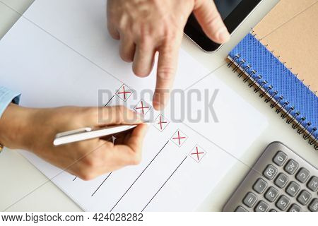Man And Woman Filling Out Questionnaire On Desktop Closeup