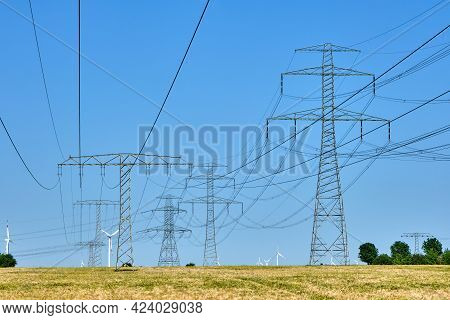 Electricity Pylons And Power Lines With Wind Turbines In The Background