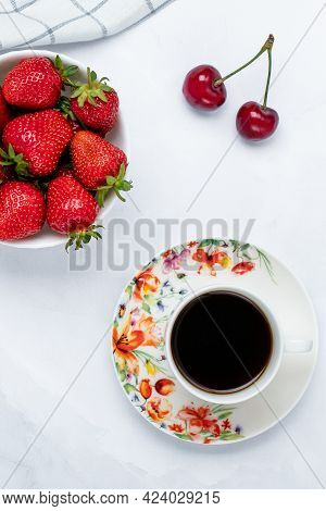 A Cup Of Black Coffee And Strawberries On A White Table. Hot Morning Drink. Red Berries, Breakfast C
