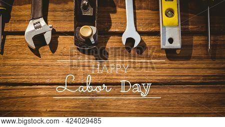 Happy labor day text and stars against multiple tools on wooden background. american labor day template background design concept