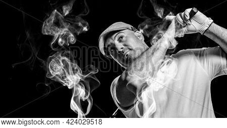 Senior caucasian male golf player swinging golf club against smoke effect on black background. sports and fitness concept