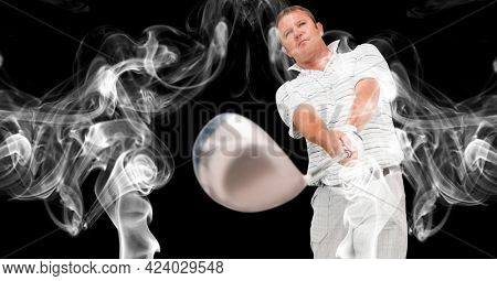 Caucasian male golf player swinging golf club against smoke effect on black background. sports and fitness concept