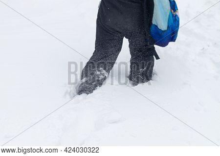A Man Walks In A Blizzard Through Deep Snow In Winter.