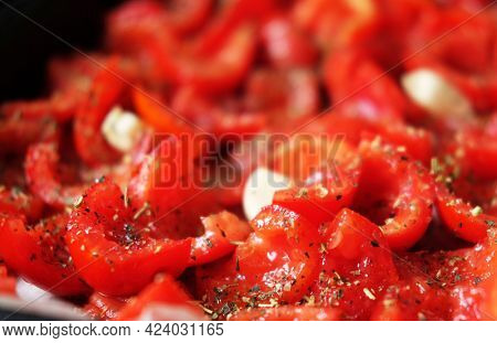 Tomatoes lie on a baking sheet, ready to bake. Sun-dried tomatoes with garlic. Food background.