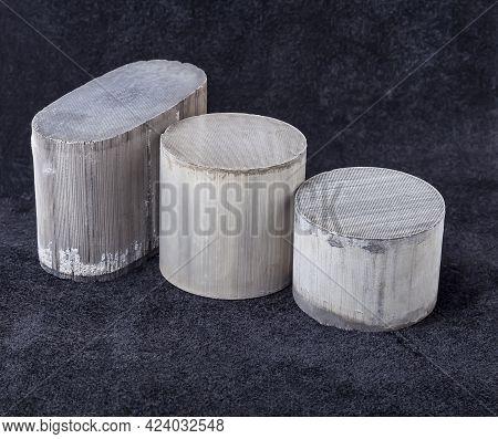 Three Round And Oval Ceramic Catalysts Containing Platinum, Palladium And Rhodium On A Black Backgro