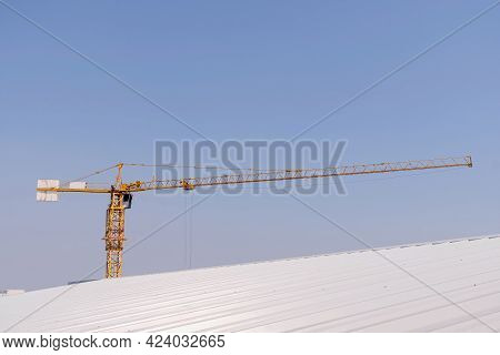 The Tower Crane Against A Blue Sky. Yellow Hoisting Crane On Blue Sky Background With Clouds, Close