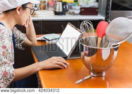 Businesswoman Baker Working On Laptop With Bakery Equipment On Table