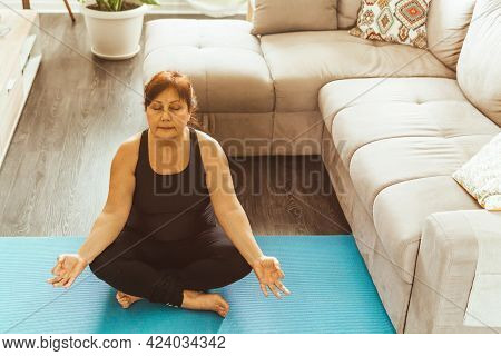 Middle Aged Woman In Sportswear In Yoga Position - Elderly Woman Relaxes Meditating In Her Home - Co