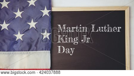 Happy martin luther king jr text on wooden slate and american flag on white background. happy martin luther king jr day template background design concept
