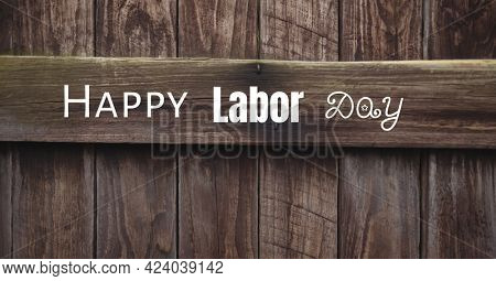Happy labor day text against wooden plank background. american labor day template background design concept
