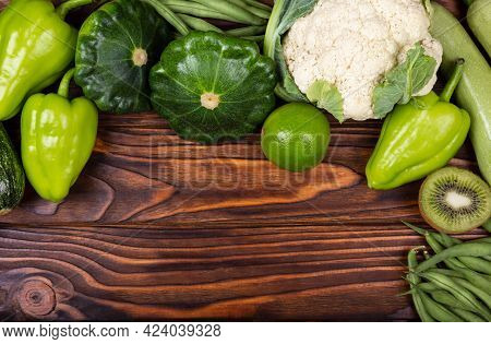Variety Of Raw Green Vegetables As Frame Over Dark Wooden Texture Background. Colorful Summer Vegeta