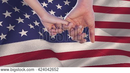 Composition of two hands linking little fingers, making pinkie promise, over billowing american flag. patriotism, independence and celebration concept digitally generated image.