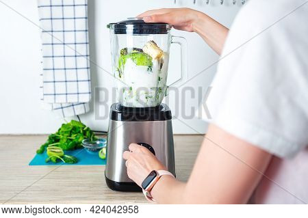 Young Woman Is Preparing Healthy Food On Light Kitchen. Green Healthy Food Concept. Vegetarian Green