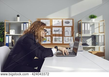 Side View Of A Funny Strange Male Office Worker Working On Laptop Sitting At Desk In Office.