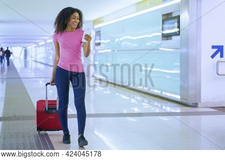 One Black Traveling Woman Holding Smartphone And Carry-on Baggage