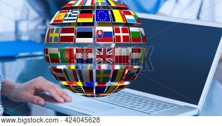Globe of flags of multiple european countries against mid section of man using laptop at office. eu union concept